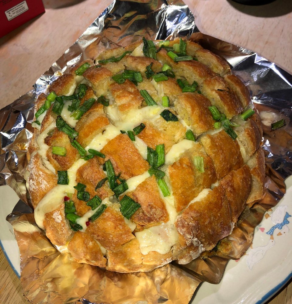 Homemade cheesy garlic pull apart bread topped with melted butter and scallions