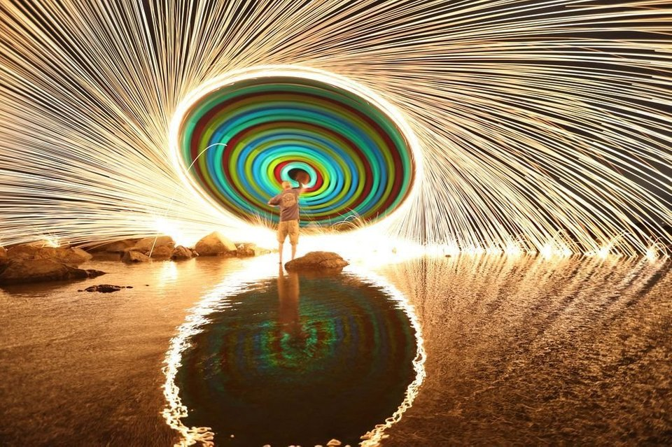What happens when you swing a string of glow sticks with burning steel wool at the end and take a long exposure photo