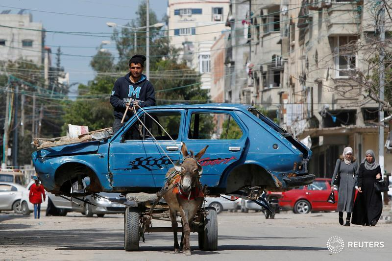 A man rides a donkey-drawn cart transporting an old car