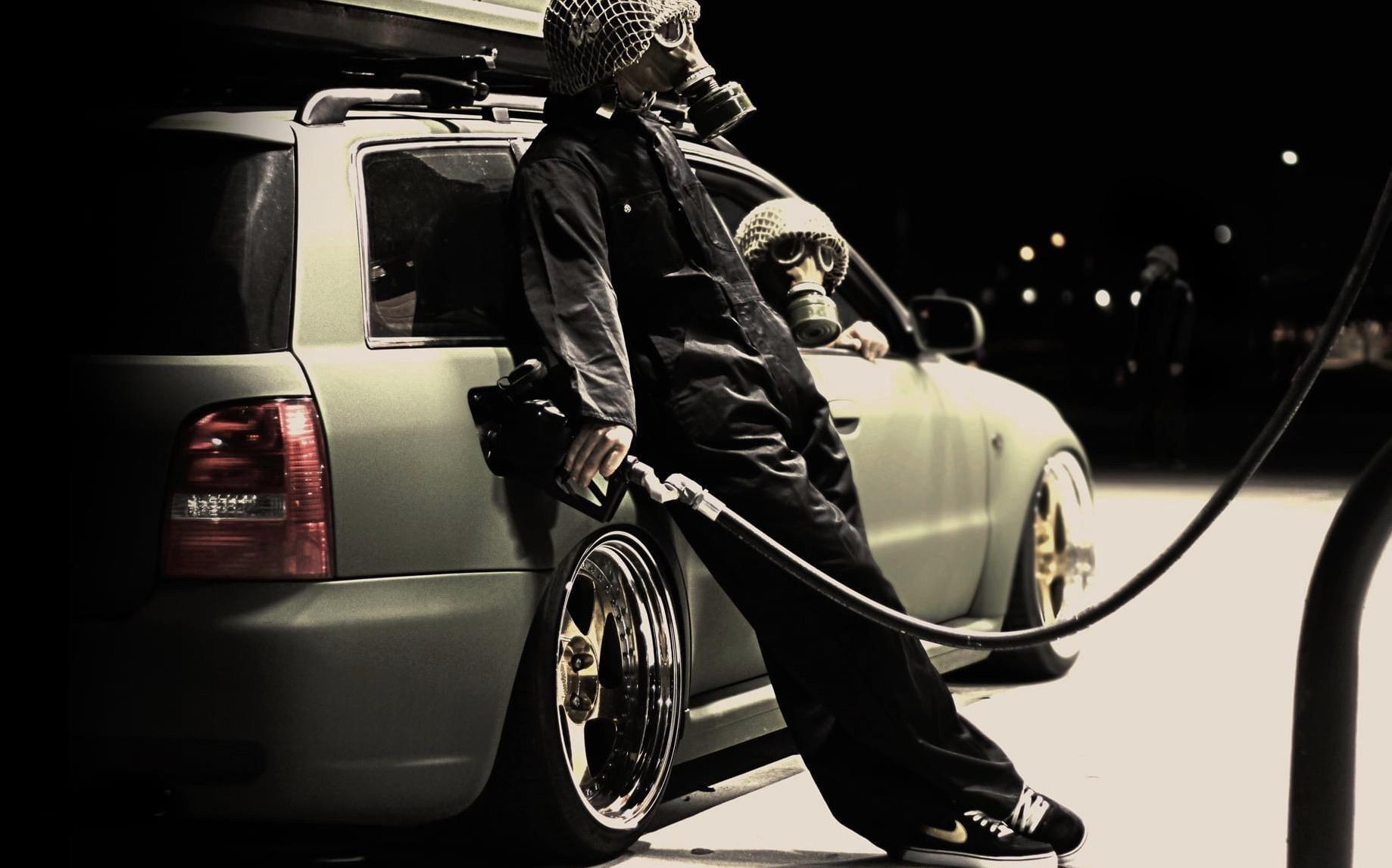 Man Fueling up an Audi wearing a Gas Mask