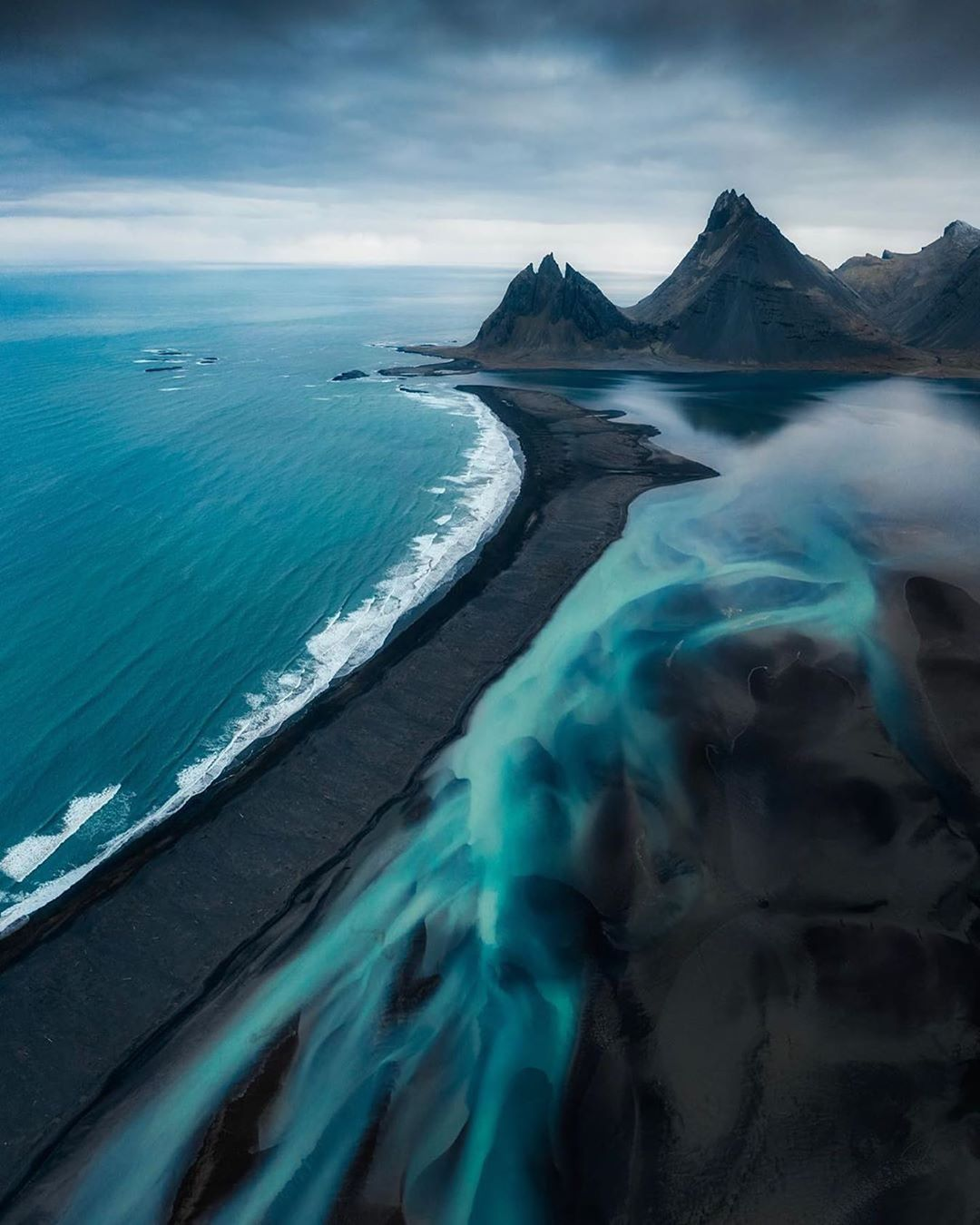 Glacial rivers meet the black sand beaches and peaks of Iceland